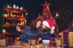 Wakacje, rodzina i ludzie pojęć, Szczęśliwa matka i mała dziewczynka w Santa pomagiera kapeluszu z sparklers w rękach, prezent zdjęcia stock