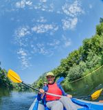 Wakacje - Szczęśliwa dziewczyna z jej matką kayaking na rzece Obrazy Stock