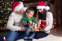 Wakacje, teraźniejszość, bożego narodzenia pojęcie - szczęśliwy matki, ojca i dziecka chłopiec otwarcia prezenta pudełko, Zdjęcia Royalty Free