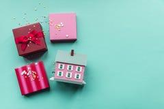Wakacji giftboxes i mini dom na pastelowym błękitnym tle Zdjęcia Stock