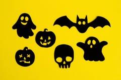 Wakacyjne dekoracje dla Halloween Czarni duchy, banie, czaszka i nietoperz na żółtym tle papierowi, odgórny widok zdjęcia royalty free