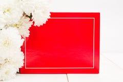 Wakacyjnego prezenta karta z czerwieni ramą z białymi kwiatami lub pudełkiem Zdjęcia Stock