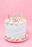 Wakacyjny domowej roboty tort dekorował z marshmallow, bezą, cukierkiem i świeczkami na pastelowych menchii tle, Ranek przy jezio Fotografia Stock