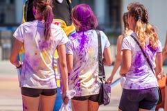 Wakacyjny holi Trzy młodej dziewczyny kropią z jaskrawymi fiołkowymi proszkami Zdjęcie Stock