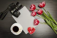 Wakacyjny pojęcie Bukiet różowi tulipany, filiżanka kawy, czerwoni sercowaci ciastka z notatką, dslr kamera i prześcieradło papie zdjęcia stock