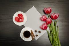 Wakacyjny pojęcie Bukiet różowi tulipany, filiżanka kawy, czerwoni sercowaci ciastka z notatką, kawałek papieru na czerni drewnia zdjęcia royalty free