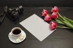 Wakacyjny pojęcie Bukiet różowi tulipany, filiżanka kawy, dslr kamera i prześcieradło papier na czarnym drewnianym tle, obrazy royalty free