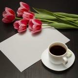 Wakacyjny pojęcie Bukiet różowi tulipany, filiżanka kawy i prześcieradło papier na czarnym drewnianym tle, zdjęcia stock