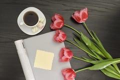 Wakacyjny pojęcie Bukiet różowi tulipany, filiżanka kawy, magazyn, pusty kawałek papieru na czarnym drewnianym tle bezpośrednio obraz stock
