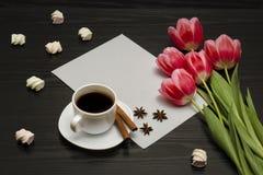Wakacyjny pojęcie Bukiet różowi tulipany, filiżanka kawy, marshmallow i prześcieradło papier na czarnym drewnianym tle, zdjęcia royalty free