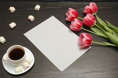 Wakacyjny pojęcie Bukiet różowi tulipany, filiżanka kawy, marshmallow i prześcieradło papier na czarnym drewnianym tle, zdjęcia stock