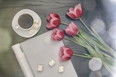 Wakacyjny pojęcie Bukiet różowi tulipany, filiżanka kawy, pusty magazyn na czarnym drewnianym tle nad bezpośrednio obraz royalty free