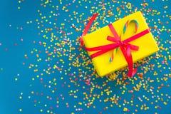 Wakacyjny prezent jest żółty niebieska tła barwioni confetti Obraz Stock