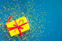 Wakacyjny prezent jest żółty niebieska tła barwioni confetti Obraz Royalty Free