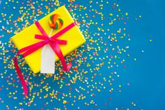 Wakacyjny prezent jest żółty niebieska tła barwioni confetti Fotografia Royalty Free