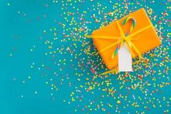 Wakacyjny prezent jest pomarańczowy niebieska tła barwioni confetti Obrazy Stock