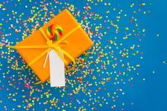 Wakacyjny prezent jest pomarańczowy niebieska tła barwioni confetti Zdjęcia Royalty Free