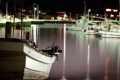 An old, small and white fishing boat parked at night on the shore. Long exposure shot and water is purplish color with reflection royalty free stock photos