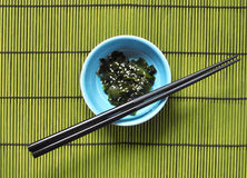 Wakame. Seaweeds with sesame seeds in a blue bowl Royalty Free Stock Image