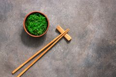 Wakame Chuka or seaweed salad with sesame seeds in bowl on dark brown rustic background. Traditional Japanese food. Top view, flat. Lay,copy space royalty free stock image