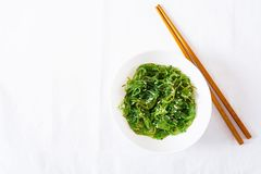 Wakame Chuka or seaweed salad with sesame seeds in bowl. On white background. Traditional Japanese food. Top view. Flat lay royalty free stock image
