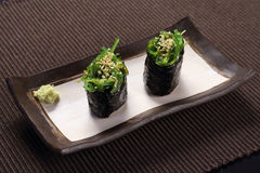 Wakame maki sushi, with wasabi on ceramic dish, seaweed  with sushi rice rolled in dried seaweed sheet Stock Photos