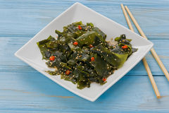 Wakame Salad. On a small white plate, with a pair of chopsticks, against a blue background Stock Photos
