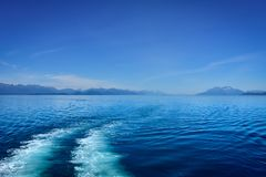 Wake Behind Boat with mountains in background. royalty free stock photos