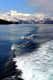 Wake behind boat with snowy mountains in background Stock Photo