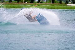 Wake board rider sliding trick with water splash. Wake boarding rider sliding trick with water splash in wake park, active sport for healthy ,recreation, hobby Stock Photography