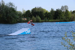Wake-boarder back flip jump at Cergy water amusement park, France Royalty Free Stock Photo