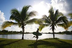 Wake Boarder Running Palm Trees. A wake boarder, backlit by the afternoon sun, runs with his board in front of palm trees, eager to begin the next skate, at Royalty Free Stock Images
