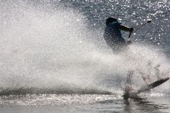 Wake Boarder Spray. A wake boarder being pulled by cable creates a gigantic plume of spray at Quiet Waters Park, Deerfield Beach, Florida Royalty Free Stock Image