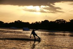 Wake Boarder at Sunset. A wake boarder getting pulled by cable waterskis, silhouetted by the evening sunset, with beams emanating from golden amber yellow clouds Stock Photo