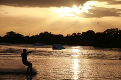 Wake Boarder at Sunset. A wake boarder getting pulled by cable waterskis, silhouetted by the evening sunset, with beams emanating from golden amber yellow clouds Stock Images