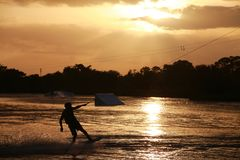 Wake Boarder at Sunset. A wake boarder getting pulled by cable waterskis, silhouetted by the evening sunset, with beams emanating from golden amber yellow clouds Stock Photography