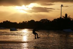 Wake Boarder at Sunset. A wake boarder getting pulled by cable waterskis, silhouetted by the evening sunset, with beams emanating from golden amber yellow clouds Royalty Free Stock Photography