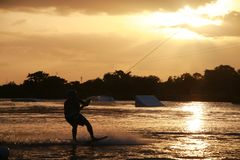 Wake Boarder at Sunset. A wake boarder getting pulled by cable waterskis, silhouetted by the evening sunset, with beams emanating from golden amber yellow clouds Royalty Free Stock Image