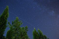 Nature banner with flight wake in the stars at night. Wake of a flight in the sky. Our galaxy is visible, as well as some cypresses following the flight line royalty free stock photo