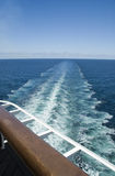 Wake and Railing. Vertical view of cruise ship wake with wooden railing in foreground Stock Photos