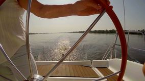 Wake from sailboat on water, woman steering boat at sunset. Stock footage stock video