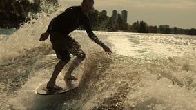 Wake surfer enjoy evening waves. Close up of rider surfing waves at sunset. Man surfing on wavws at sunset stock footage