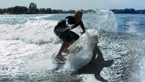 Wake surfer falling in water in slow motion. Man rotating on wake surf