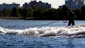 Wake surfer riding board on river in sunny day. Extreme lifestyle concept