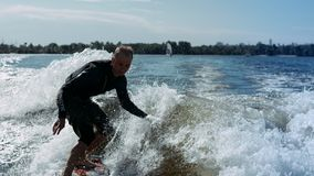 Wake surfing rider enjoy waves. Sportsman surfing on waves in slow motion. Water extreme lifestyle stock video footage