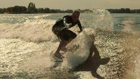 Wake surfing rider training stunt. Wakesurfer falling into water stock footage