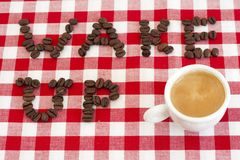Wake up!. Wake up spelled with coffee beans with a cup of espresso Stock Photos