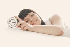 Wake up. Woman - turning off alarm clock. Focused on alarm clock. Auburn tint royalty free stock photo