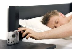 Wake up. Man reaching for alarm clock Royalty Free Stock Image
