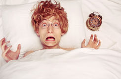Wake up. Funny guy woken up by an alarm clock Stock Photography